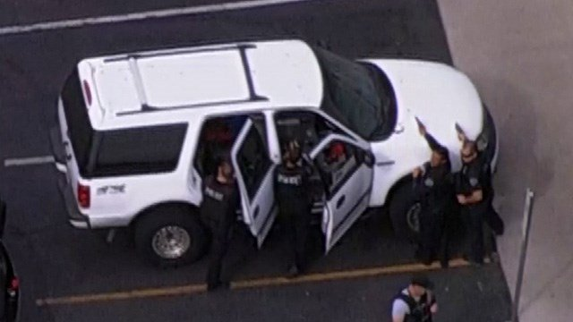 Police with guns drawn surround a vehicle at a gas station in Mesa believed to contain a Chandler robbery suspect. (Source: KPHO/KTVK)