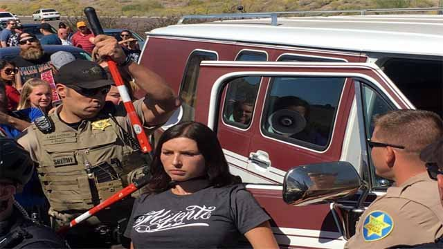 Woman being freed from tied around her car. Unclear if she tied herself or not. (Source: Justin Emerson/Cronkite News)
