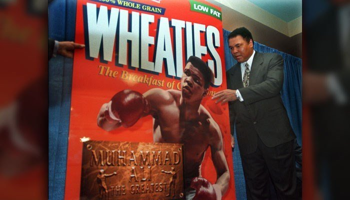 """Muhammad Ali, known as """"The Greatest,"""" poses next to a Wheaties """"The Breakfast of Champions"""" poster during the unveiling of the 75th Anniversary cereal box in his honor in New York, Thursday Feb. 4, 1999. (AP Photo/Bebeto Matthews)"""