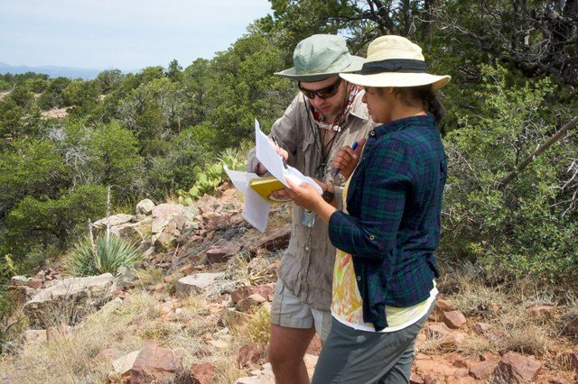 ASU graduate students Daniel Dunlap and Prajkta Mane consult their notes while looking for meteorites in the White Mountain Apache tribal lands. (Source: Laurence Garvie, ASU)