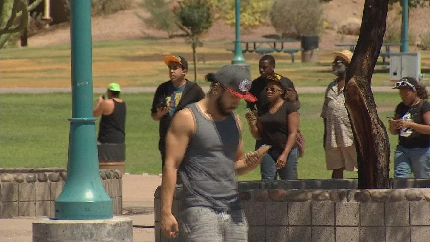 People are still glued to their phones but are outside playing Pokémon Go. (Source: KPHO/KTVK)