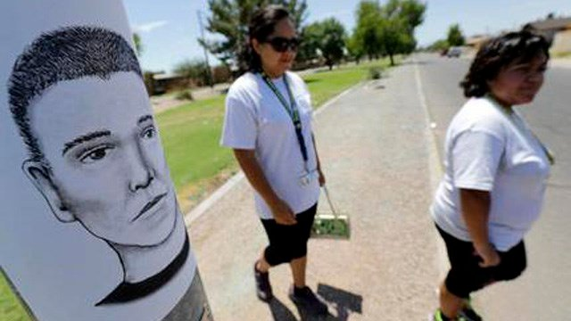 In this July 27, 2016 photo, neighborhood patrol officers Maribel Diaz Lopez, left, and Mario Ocampo walk Maryvale neighborhood streets in Phoenix to hand out an artist rendering of a suspected serial killer. (Source: AP Photo/Matt York)