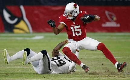 Arizona Cardinals' Michael Floyd (15) gets pulled down by Oakland Raiders' David Amerson (29) after a long pass reception during the first half of an NFL preseason football game Friday, Aug. 12, 2016, in Glendale, Ariz. (Source: AP Photo/Ross D. Franklin)