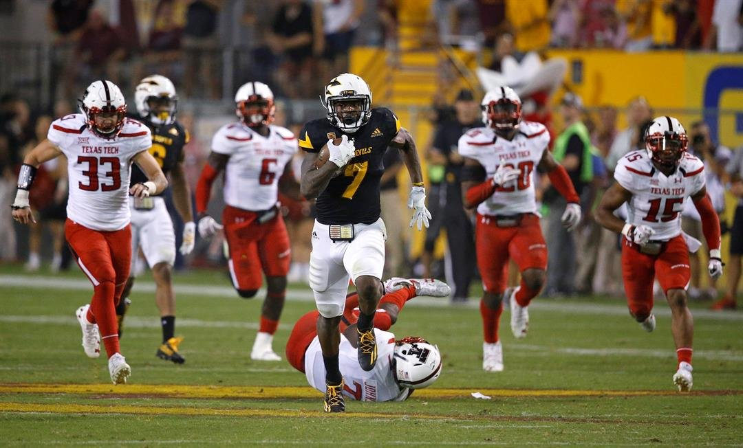 Kalen Ballage breaks away for one of his record-breaking 8 touchdowns (AP Photo/Ross D. Franklin)