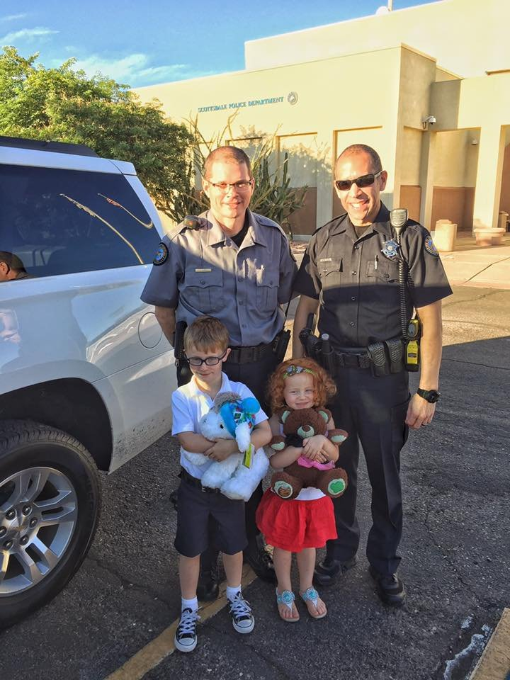 Officer Kory Sneed (right) and his partner with the Scottsdale Police Department pose for a picture with Fortin's children have giving them a seat belt safety lesson. (Source: Michelle Fortin)