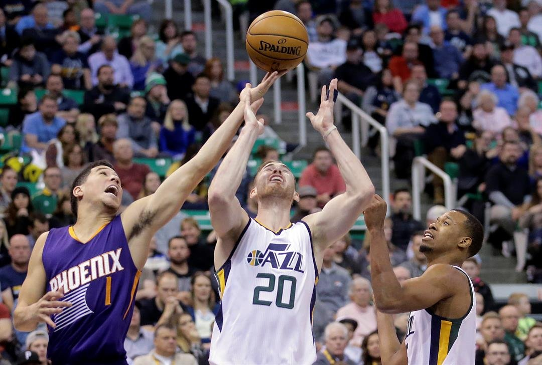Phoenix Suns guard Devin Booker (1) battles with Utah Jazz's Gordon Hayward (20) and Rodney Hood, right, for a rebound in the first half during an NBA basketball game Tuesday, Dec. 6, 2016, in Salt Lake City. (Source: AP Photo/Rick Bowmer)