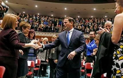 Arizona Republican Gov. Doug Ducey, center, shakes hands with Rep. Heather Carter, left, R-Cave Creek, as he arrives on the House of Representatives floor to give his State of the State Address. (AP Photo/Ross D. Franklin)