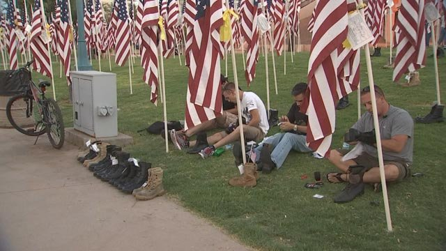 Alan Blume, an Iraq War veteran, and three other military men sat in the field of flags for hours on 9/11. (Source: KPHO/KTVK)