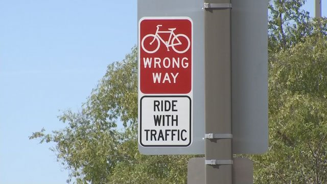 Workers placed 55 stickers on existing signs to alert bicyclists going against traffic that they are riding the wrong way.  (Source: KPHO/KTVK)