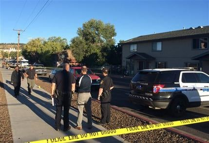 Authorities gather outside a student dormitory in Flagstaff, Ariz., Friday, Oct. 9, 2015, after an early morning fight between two groups of college students escalated into gunfire leaving one person dead. (AP Photo/Felicia Fonseca)