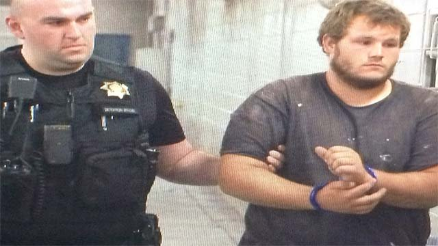 Merritt in handcuffs prior to booking on Sept. 18.. (Source: KPHO.KTVK)
