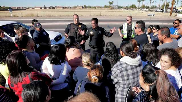 A Glendale police officer tries to give instructions to parents waiting to reunite with their children. The danger at the campus was over, police said, as worried parents crowded stores nearby to await word on their children. (AP Photo/Matt York)