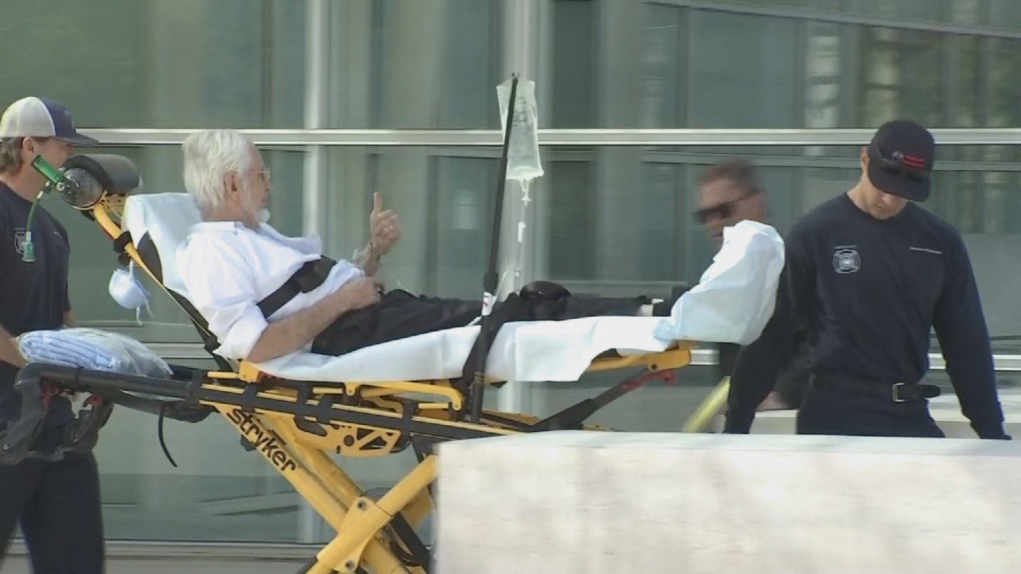 Federal Judge Russel Holland is wheeled out of the courthouse after falling ill on the bench Monday morning. (Source: KPHO/KTVK)